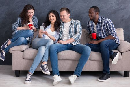 Happy girl showing photos and video on her smartphone to friends. Mixed race people sitting on the couch at home Banco de Imagens