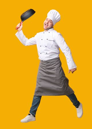 Funny Male Chef Jumping Posing With Frying Pan Having Fun Over Yellow Studio Background. Vertical, Full Length Stock fotó