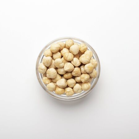 Pile of hazelnuts in glass bowl on white background, top view