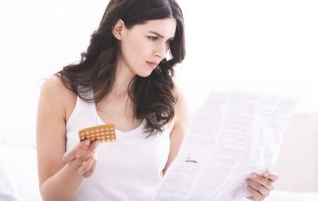 Medical side effects. Worried woman reading medicament instruction of oral contraceptive pills, free space