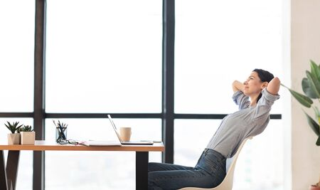 Time For Break. Successful young woman stretching hands, leaning back in her chair at workplace, copyspace Stock Photo