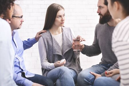 Calm Down. Concerned therapy group members comforting upset woman at community meeting in rehab, offering glass of water