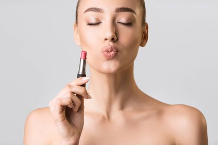 Makeup Concept. Model Girl Holding Lipstick Posing With Closed Eyes On Gray Studio Background.