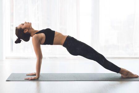 Purvottanasana Or Upward Plank Pose. Beautiful sporty girl practicing yoga on mat, stretching body, copyspace