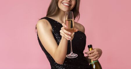 Unrecognizable girl offering glass of champagne at camera, posing over pink background in studio, cropped image, panorama