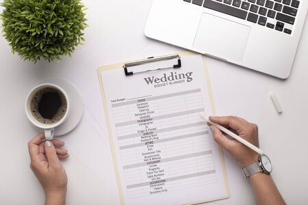 Woman planning her wedding, calculating budget and searching services on laptop, white table background