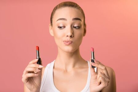 Makeup. Beautiful Woman Holding Two Lipsticks Choosing Lipgloss For Daily Make-Up Standing On Pink Studio Background.