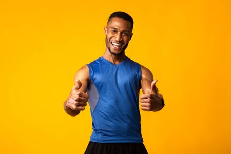 Go In For Sports. Happy muscular black man showing thumbs up gesture isolated over yellow studio wall. Copyspace