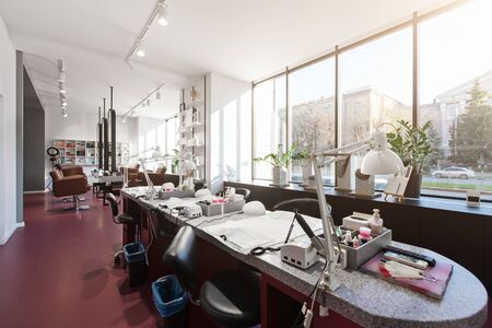 Interior of luxury stylish beauty salon. Tables for manicure with professional tools, panoramic windows. Pink concept design
