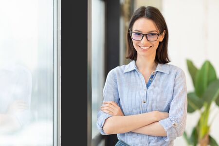Successful Businesswoman. Portrait of confident european girl in glasses standing next to window, looking at camera