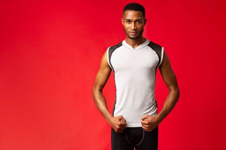 Personal Trainer. Confident black sports man standing in stance isolated over red wall, looking at camera, copyspace Banco de Imagens