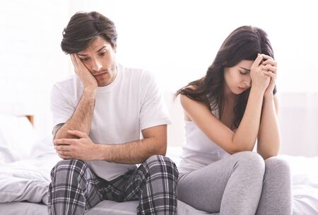 Marital crisis. Desperate man and woman sitting on bed after hard talk
