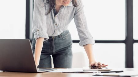 Office Work. Unrecognizable female manager standing at desk using laptop and touching tablet, copyspace