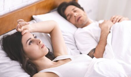 Hormonal disbalance. Young woman suffering from insomnia, husband sleeping aside, panorama Stok Fotoğraf