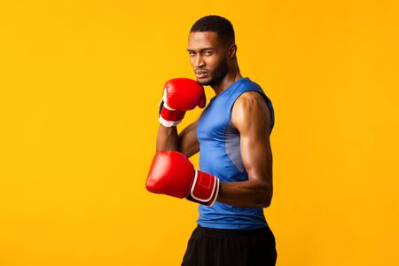 Professional Box Concept. Muscular athletic black boxer showing defending pose, yellow studio wall, empty space