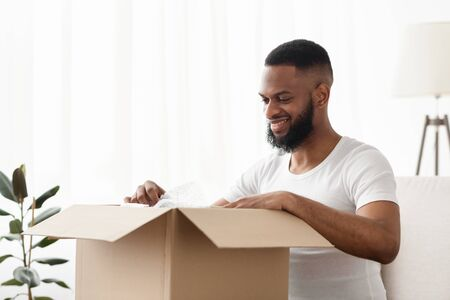 Online Store and home delivery. Excited afro american man get a package, free space