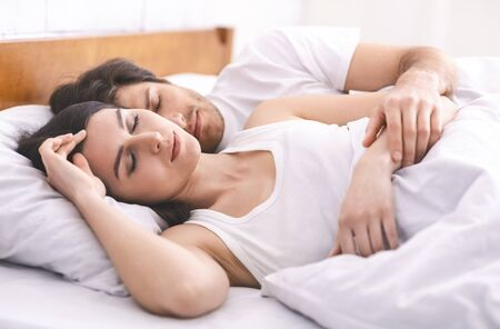 Young married couple sleeping together in bed, close up Stok Fotoğraf