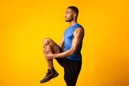 High Knees Exercise. Side view of black guy warming up before training, lifting leg over yellow wall, copyspace Foto de archivo