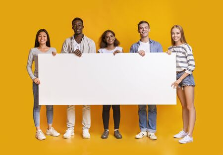 Smiling group of multiracial students standing together in row and displaying white empty placard, yellow studio background