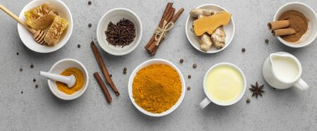 Traditional Indian drink turmeric milk is golden milk with cinnamon, honey, curcuma root and turmeric powder. Hot healthy drink. Concrete background, panorama