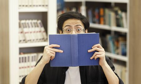 Oh No. Scared anxious korean student guy hiding face behind book in modern university library, copyspace