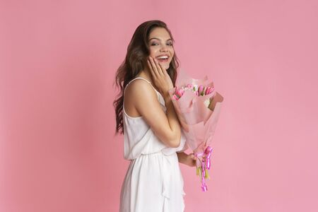 Surprised young woman gets bouquet of tulips as present for International Womens Day, touching cheek in excitement, posing over pink background Banco de Imagens