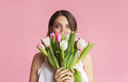 Playful young girl covering face with bouquet of tulips, sniffing flowers, posing over pink background with free space Banco de Imagens