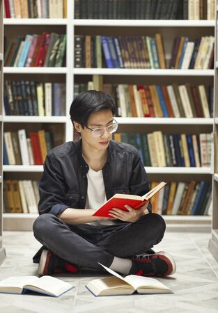 Bookworm Concept. Creative asian male student sitting on the floor and reading a book at library, free space