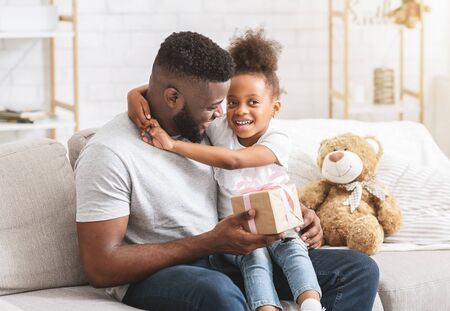 I wish you all the best daddy. Adorable african little girl sitting on dads lap, father holding gift box, celebrating birthday together at home