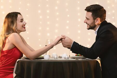 Romantic couple holding hands, celebrating their anniversary on date in restaurant, looking at each other with love and affection, side view