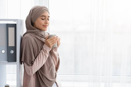 Start Of The Work Day. Relaxed Arabic Businesswoman Drinking Coffee, Holding Cup, Standing Near Window In Office, Free Space Stok Fotoğraf