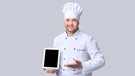 Online Menu. Chef Man Holding Digital Tablet Showing Empty Screen Recommending Catering Service Standing On Gray Background. Mockup, Panorama