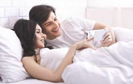 Happy memories. Young married couple watching photos on cellphone, resting in bed