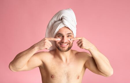Male body care concept. Cute young man after a shower, white towel on head, smears cream on face. Reklamní fotografie