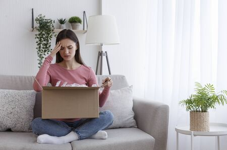 Negatively surprised girl sitting on coach and looking into cardboard box with wrong or damaged item, home interior, copy space Banque d'images