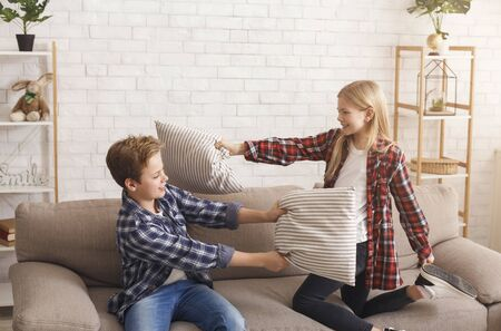 Pillow Fight. Siblings Boy And Girl Having Fun Playing Together Fighting With Pillows Sitting On Couch Indoor