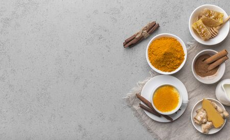 Tasty hot turmeric curcuma milk in cup on gray concrete table arranged with turmeric roots and spices, copy space