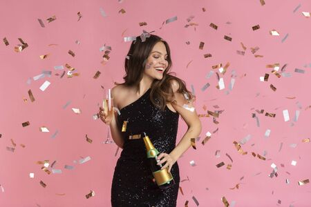 Festive Mood. Joyful woman in evening dress with champagne bottle and filled glass in hand posing over pink background with falling confetti