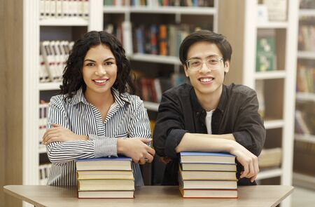 Front view of two smiling multicultural students leaning on pile of books and looking at camera sitting in modern library