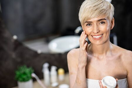 Facial Skin Care. Middle-Aged Woman Applying Cream On Face Holding Cosmetic Product Jar Smiling To Camera Standing In Bathroom. Copyspace