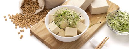 Organic Soy Tofu, Microgreens on a wooden board. Sprinkled soy beans, chopsticks Banco de Imagens