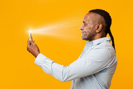 Mature african man scanning his face with mobile app, free space Imagens