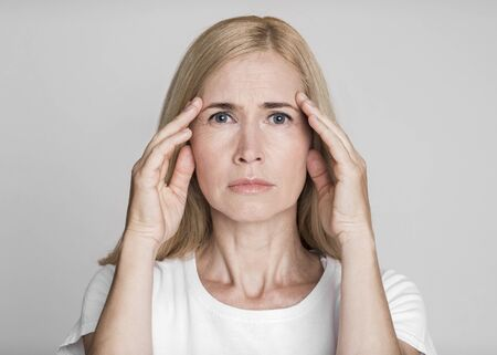 Blonde middle-aged woman touching her temples, suffering from migraine