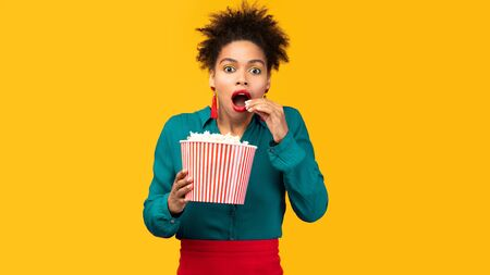 Shocked black girl watching film and eating popcorn isolated over yellow wall