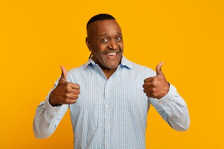 Enthusiastic mature afro american man gesturing thumbs up with both hands