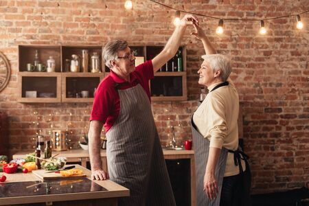 Romantic elderly couple dancing together while cooking in kitchen