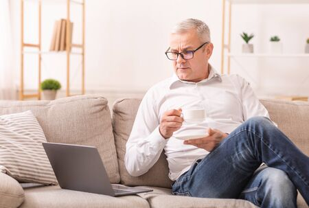 Focused Senior Man In Glasses Using Laptop And Drinking Hot Tea, Sitting On Couch