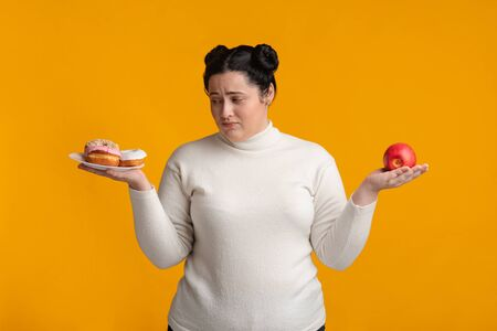Eat Or Not To Eat. Undecided plump woman choosing between healthy and unhealthy food
