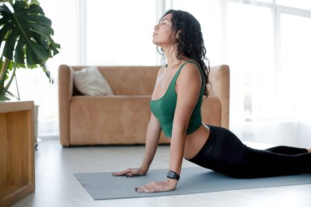 Sports and home fitness concept. Attractive Hispanic woman doing yoga exercises indoors. Cobra pose Banco de Imagens