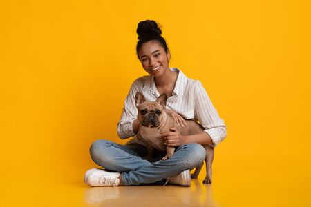 Animal Lover. Young pretty african american woman sitting together with her french bulldog dog puppy and hugging him, yellow background